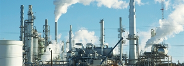 Oil refinery smoke stacks and machinery against a blue sky