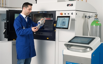 ADDvance O2 precision box with EOS 3D printer and employee holding/looking at a 3D printed object.