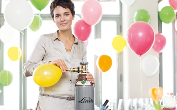 Hospitality & Leisure: Lady inflating balloons (with Linde gas) for an event