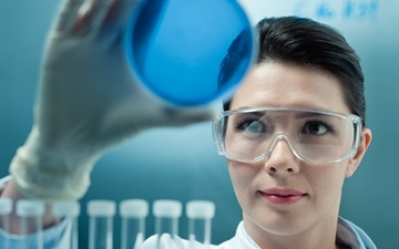Woman in laboratory holding a petri dish