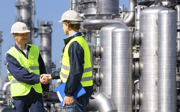 Two workers standing outside of a refinery