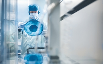 Electronics worker holding silicon wafer by cutting machine in clean room.