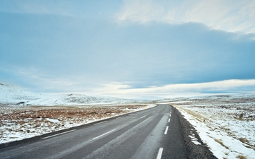 Empty road inthe countryside of Iceland with a little snow on the side of the road.